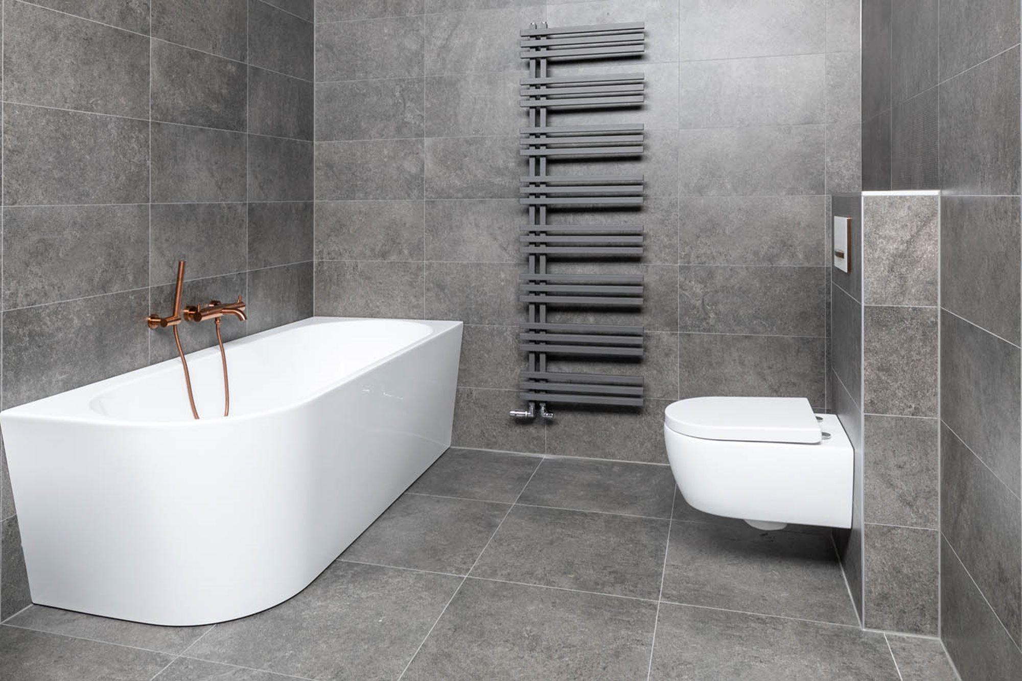 breedte-bad-verschillende-maten-halfvrijstaand-bad-koperen-kraan-grijze-radiator-grijze-tegels-hangtoilet.jpg